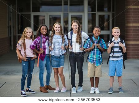 Large Group portrait of pre-adolescent school kids smiling in front of the school building. Back to school photo of a diverse group of children wearing backpacks and ready to go to school