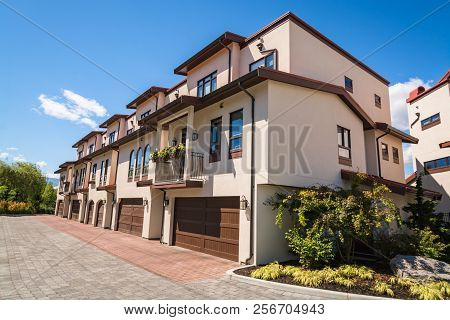 Residential Townhouses With Paved Driveway And Wide Garage Door. Residential Townhouses On Blue Sky