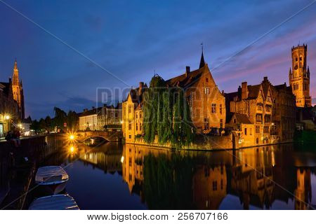 Famous view of Bruges tourist landmark attraction - Rozenhoedkaai canal with Belfry and old houses along canal with tree in the night. Brugge, Belgium