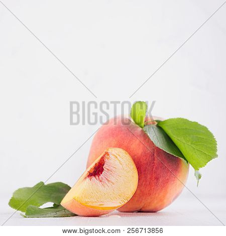 Elegance Ripe Peach With Green Young Leaves And Juicy Piece On White Soft Wood Background, Copy Spac