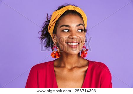 Image of charming woman 20s in hair band and earrings smiling and looking aside isolated over violet background poster
