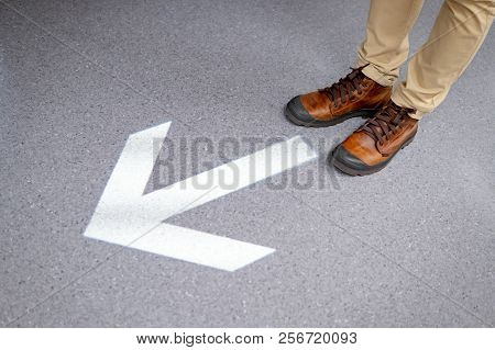 Male Feet With Casual Shoes Standing Over Light Arrowhead Go Forward Sign On The Floor. Keep Moving