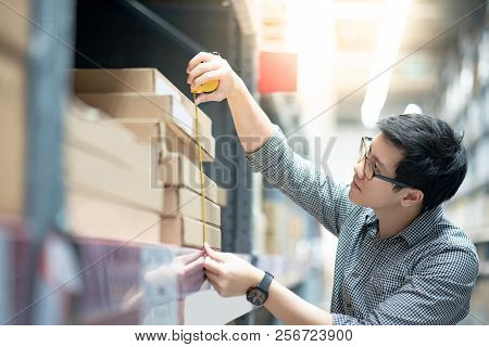 Young Asian Man Worker Using Tape Measure For Measuring Dimension Of Product In Cardboard Box. Shopp