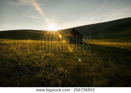 Sunset In Countryside Landscape. Fields And Countryside Landscape. Old Cabin In Meadow Sunset. Natur