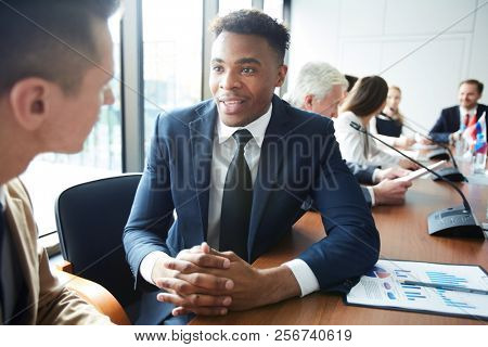 Portrait of African-American businessman talking to colleague while sitting at meeting table in conference room, copy space