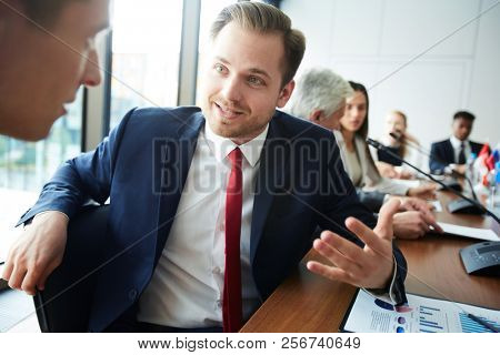 Portrait of mature businessman talking to colleague while sitting at meeting table in conference room, copy space