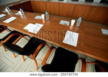 Background image of empty conference table with water bottles and sheets of paper prepared for important business meeting, copy space