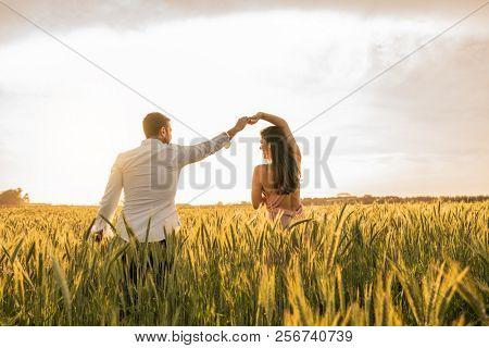 Romantic Couple Dancing on Love Moment at gold wheat field