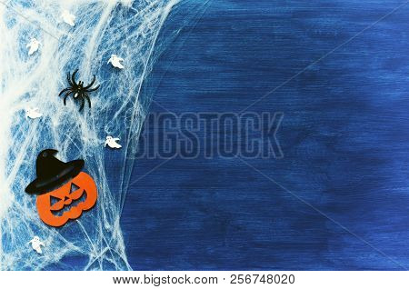 Halloween background. Spider web, spiders and smiling jack decorations - the symbols of Halloween on the dark blue wooden background, free space for Halloween text