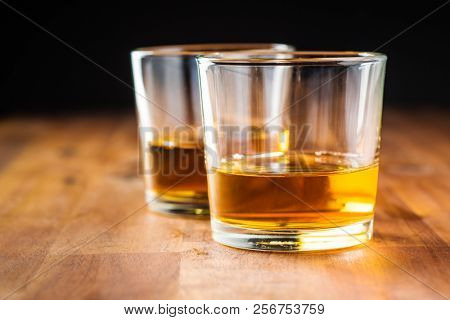 Glass of alcoholic drink wooden table. Whiskey in glass.