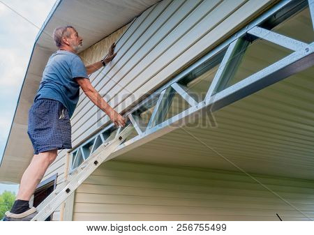 man working on a wall with plastic siding