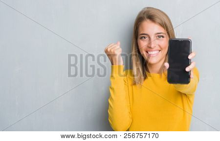 Beautiful young woman over grunge grey wall showing smartphone screen screaming proud and celebrating victory and success very excited, cheering emotion