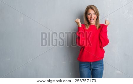 Beautiful young woman standing over grunge grey wall wearing winter sweater screaming proud and celebrating victory and success very excited, cheering emotion