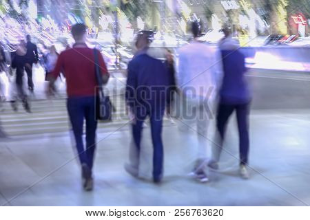 Abstract Background Of Four Young People, Walk On City Street In Evening. Intentional Motion Blur. C