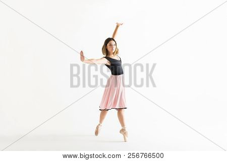 Full Length Of Confident Young Ballerina Dancing Gracefully On White Background