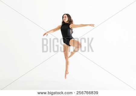 Attractive Young Ballerina In Midair With Arms Outstretched Over White Background