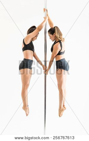 Full Length Of Women In Midair Practicing Pole Dance Against White Background
