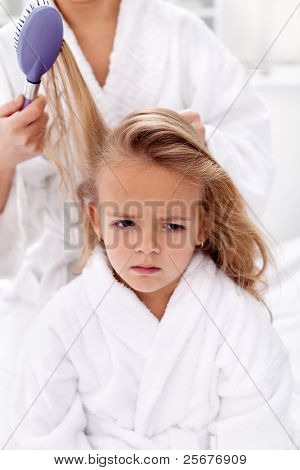 The price of  beauty is pain - little girl sulking while combing