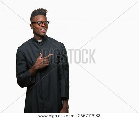 Young african american priest man over isolated background cheerful with a smile of face pointing with hand and finger up to the side with happy and natural expression on face looking at the camera.