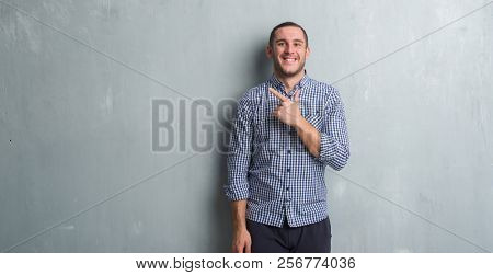 Young caucasian man over grey grunge wall cheerful with a smile of face pointing with hand and finger up to the side with happy and natural expression on face looking at the camera.