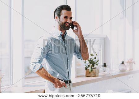 Young Smiling Business Man Talking On Phone. Handsome Happy Bearded Man Standing Next To Window And
