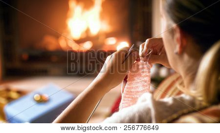 Closeup Image Of Woman With Knitting Needles And Wool Sitting By The Fireplace