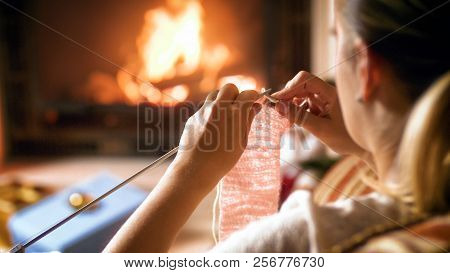 Closeup Photo Of Young Woman Warming By The Fireplace While Knitting Woolen Scarf