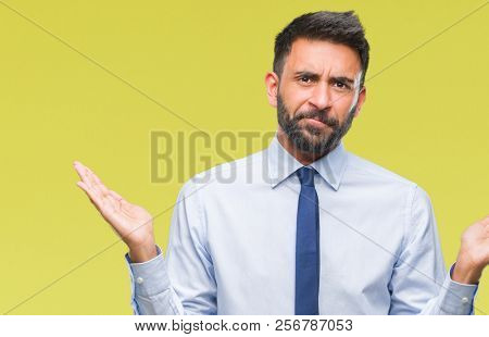 Adult hispanic business man over isolated background clueless and confused expression with arms and hands raised. Doubt concept.