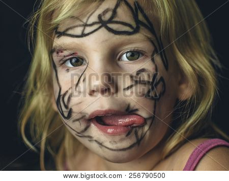 The little girl painted her face with a marker. Makeup for Halloween