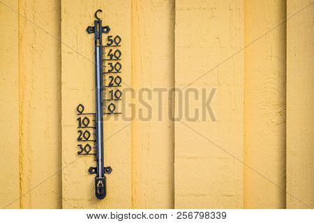 Weather Thermometer Hanging On A Yellow Wall On Wooden Planks