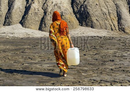 Woman In A Sari And Hijab Carries A Plastic Jerrican With Water Over A Lifeless Desert Valley
