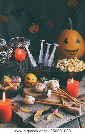 Halloween Trick Or Treat Party. Funny Delicious Sweets And Pumpkin On Wooden Background - Muffins, C