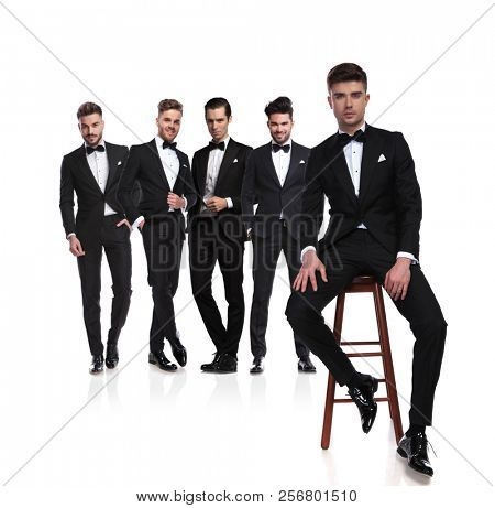 group of five elegant young men in black tuxedoes with leader sitting on chair in front of them, on white background, full body picture