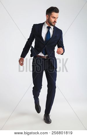 confident businessman in navy suit walking on light grey background while looking down to side, full length picture