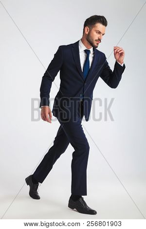 side view of confident businessman in navy suit stepping on light grey background, full length picture