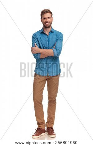 confident smiling casual man with hands crossed in a full body pose on white background