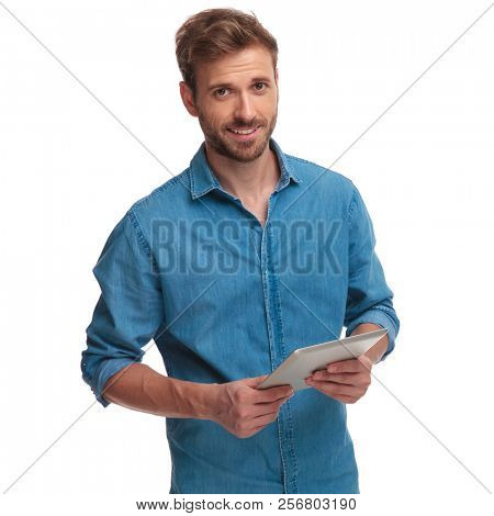 happy casual man holding ebook smiles at the camera on white background
