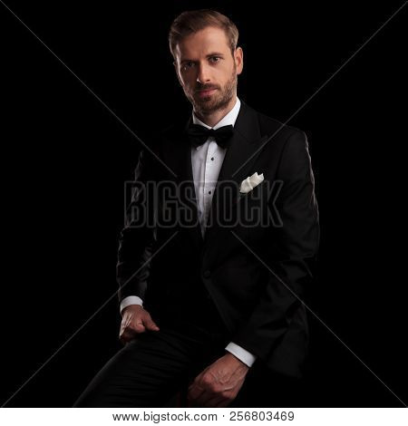 young elegant man in tuxedo resting on a chair on black background
