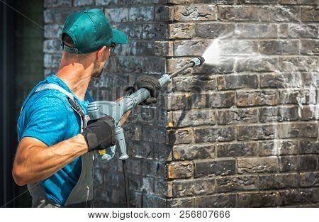 House Brick Wall Washing Using Pressure Washer. Caucasian Worker In His 30s.