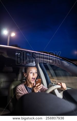Young female driver playing with her cellphone instead of paying attention to driving, startled in a potentially dangerous situation - Road safety concept