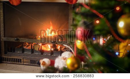Closeup Image Of Burning Fireplace In Living Room At House With Decroated Christmas Tree