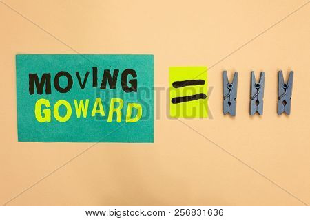 Handwriting text Moving Goward. Concept meaning Towards a Point Move on Going Ahead Further Advance Progress Turquoise paper reminder equal sign several clothespins sending message. poster