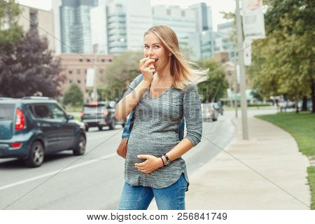 Happy Healthy Pregnancy. Portrait Of Caucasian Pregnant Young Blonde Caucasian Woman Eating Apple .