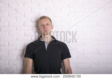 Young Man In Stylish Black T-shirt Against White Brick Wall. Black T-shirt Mockup For Design. Man We