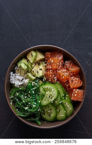 poke bowl with salmon over dark background. top view poster