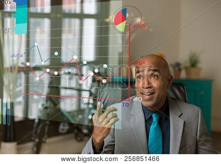 Business Man Pointing To Figures On A Futuristic Graph