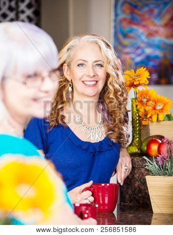 Woman Smiling In Kitchen With Her Friend