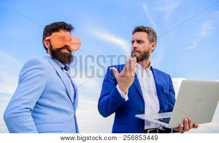 Businessman With Laptop Serious While Business Partner Ridiculous Glasses Looks Funny. Ways To Get P