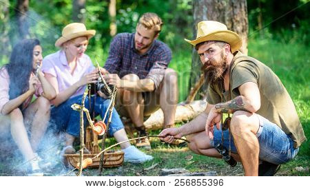 Hipster Roasting Sausage While Friends Sit On Log Sharing Impression And Watching Photos On Camera.