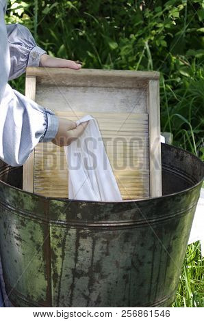 Girl Dressed As Pioneer Washing Laundry Outside With Washboard In Summer